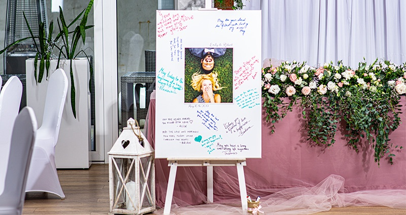 A big canvas with a photo of a couple in love in the middle, with guests' wishes written with a marker pen around it. A white lantern is placed next to the canvas, with a table ornamented with powder pink netting and flowers in the background.