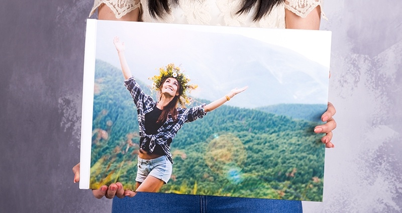 A woman holding a closed photo book A3 Landscape, focus on the cover with a girl wearing a wreath in the mountains