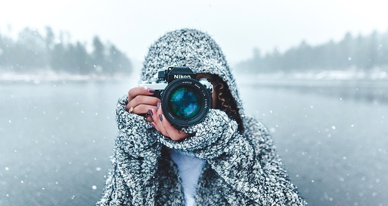 A woman taking photos on a lake background