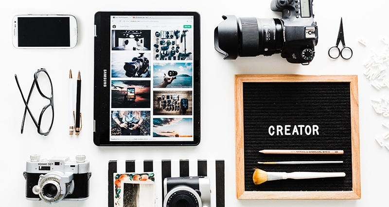 "Cameras, smartphone, tablet and other gadgets on a white desk next to a blackboard in a wooden frame with a text ""Creator"""