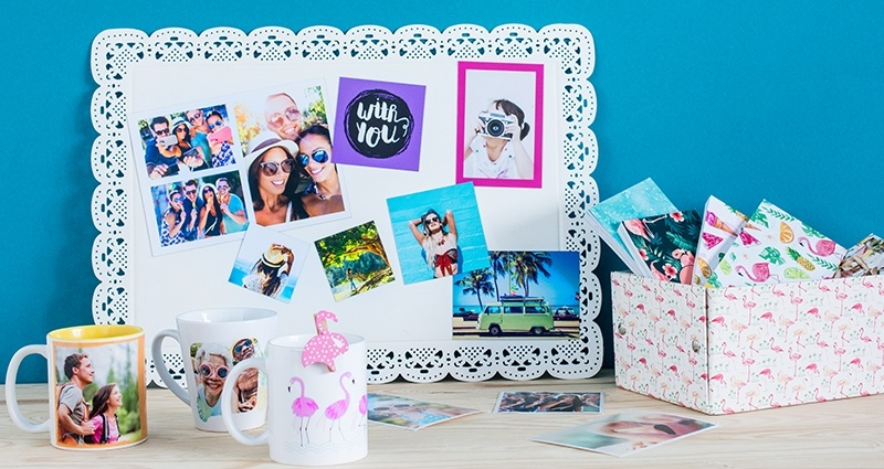 Collection of summer photo products lying on the desk – photo magnets on a white board, sharebooks in a box, photo mugs (coloured and latte) and photo prints