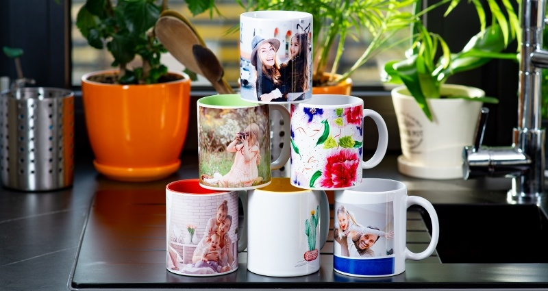 Coloured spring themed mugs arranged in a pyramid on a kitchen sink. Window and plants in the background.