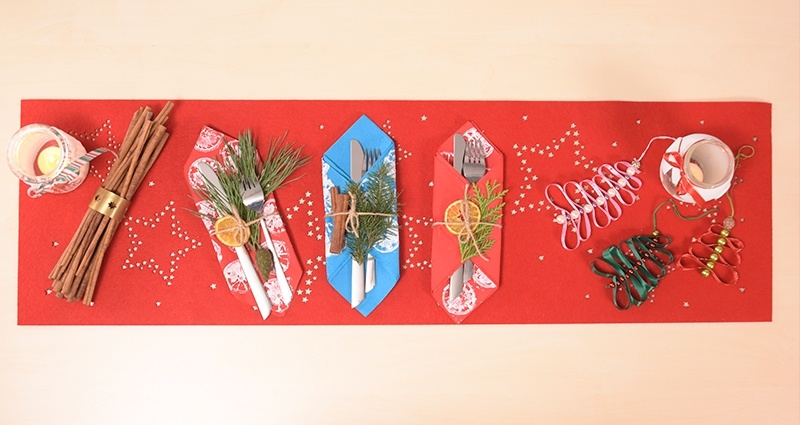 DIY Christmas decorations: decorative cutlery pockets, jar lanterns and Christmas trees made of ribbons on a red napkin, long cinnamon sticks on the left side
