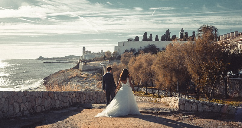 A photo of newlyweds on a rocky path near the seaside in Autumn.