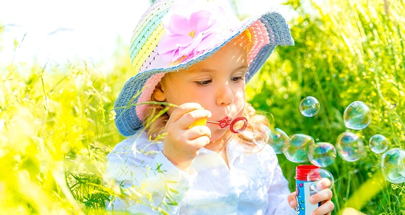 Kid blowing bubbles in the meadow