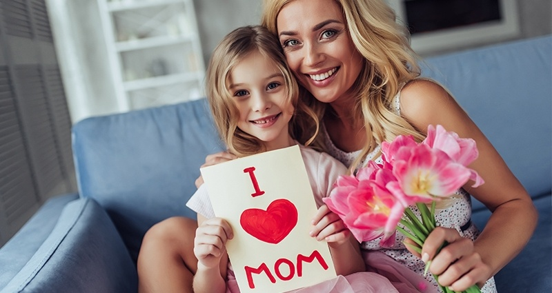 "Mom and daughter are sitting on a grey couch. Mom is holding a bouquet of flowers and the girl a Mother's Day card with the ""I <3 MOM"" caption."