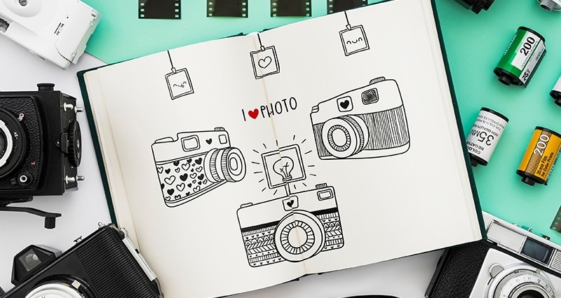 "Open book with three drawn cameras and the ""I <3 photo"" writing on its pages; cameras, lenses and films around the book lying on a mint mat on a white desk"