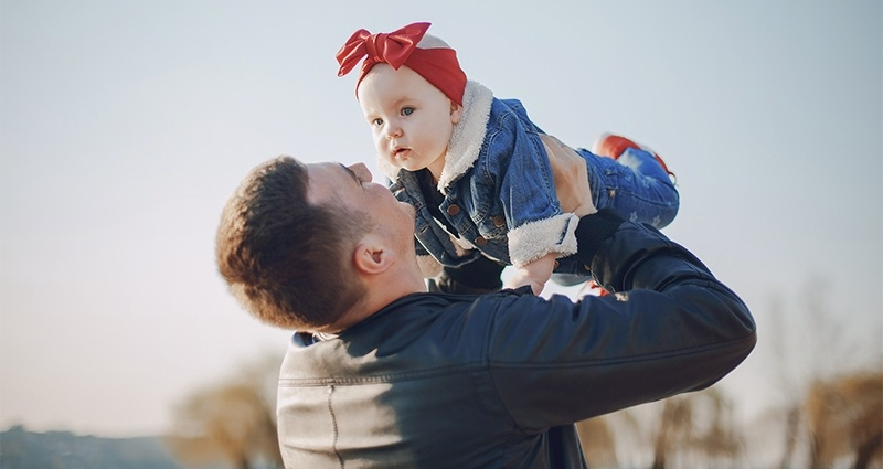 Father playing with his little daughter wearing a red bow