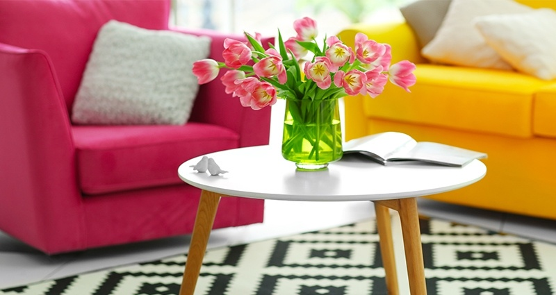 Photo of a coffee table on a black&white rug with a vase full of pink tulips. Amaranthine armchair and yellow couch in the background.