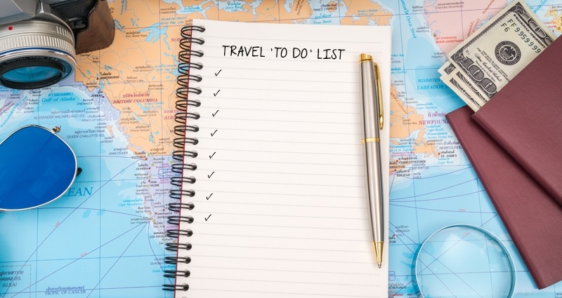 Spiral notebook, passport, money, camera and sunglasses, colourful map as the background