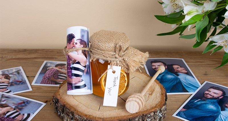 A jar of honey decorated with jute and a rolled up print on a wooden disc, a honey dipper and prints of a young couple next to it and white flowers bouquet in the background.