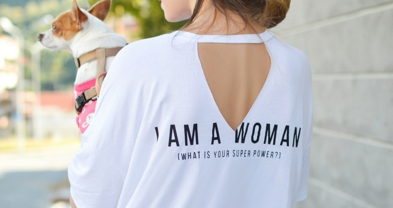 "Woman in a t-shirt with inscription on the back ""I'm a woman, what's your superpower?"""