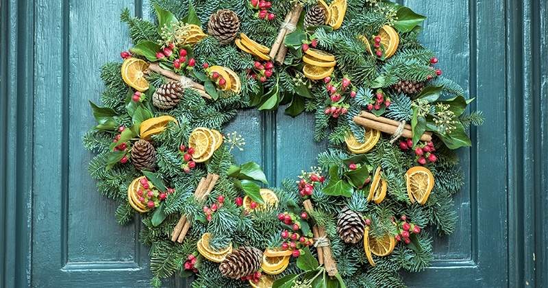 Wreath with lemons, cinnamon and cones, hanged on the door